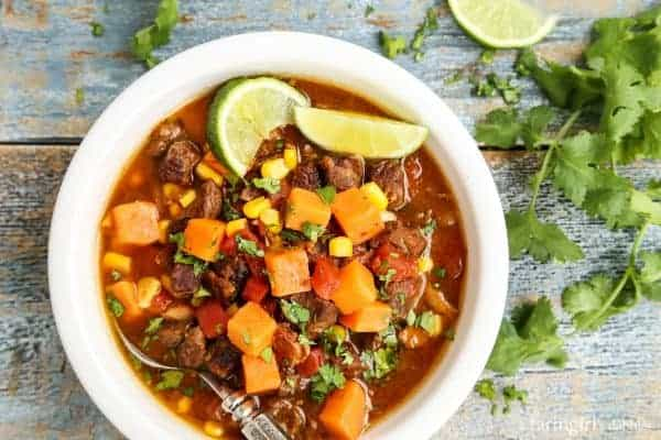 a white bowl Slow Cooker Beef and Sweet Potato Soup with fresh cilantro and lime