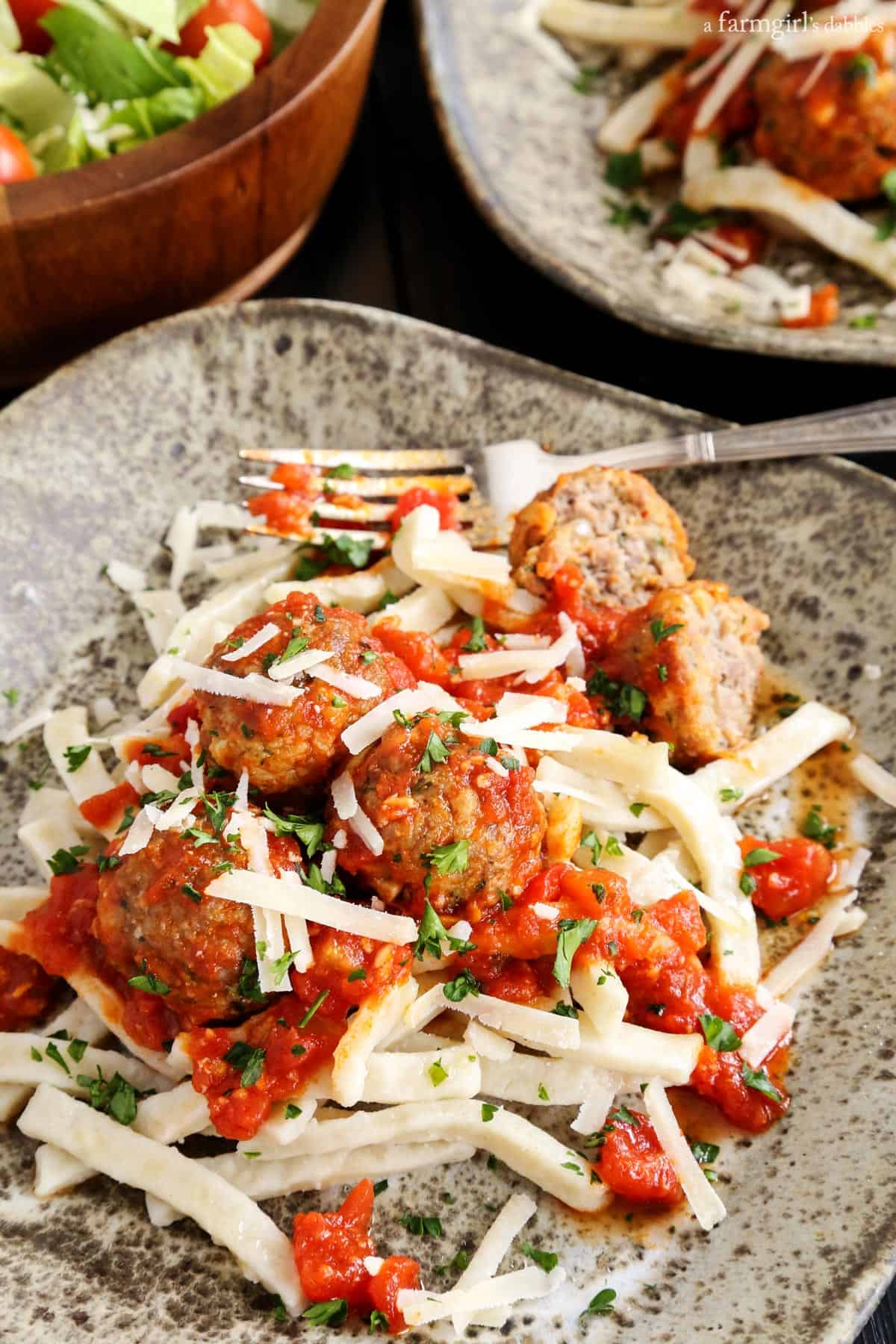 Spicy Italian Sausage Meatballs over Egg Noodles from afarmgirlsdabbles.com