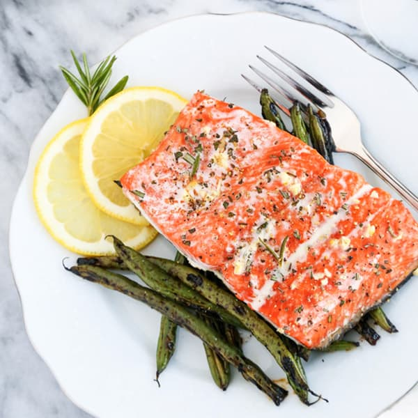 Roasted salmon filet on a white plate with green beans, rosemary and lemon slices