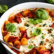 A white bowl of gnocchi with tomato sauce, melted cheese and fresh basil leaves