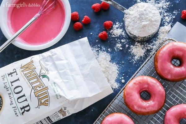 Yeast Donuts with Raspberry Glaze surrounded by flour, raspberries and a bowl of glaze