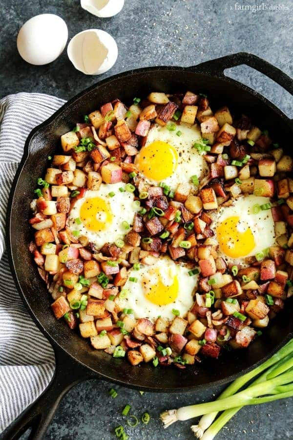 Overhead view of a cast iron skillet with potato hash topped with eggs
