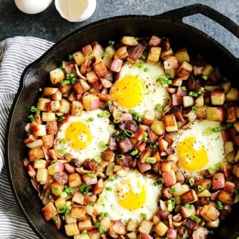 skillet of fried potatoes hash with eggs and bacon