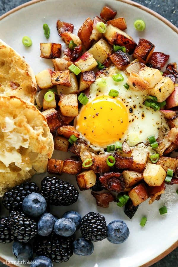 potato hash on a plate with English muffin and fresh blueberries and blackberries