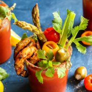 A glass of Bloody Mary with Grilled Jalapeno Shrimp, Celery, and Olives