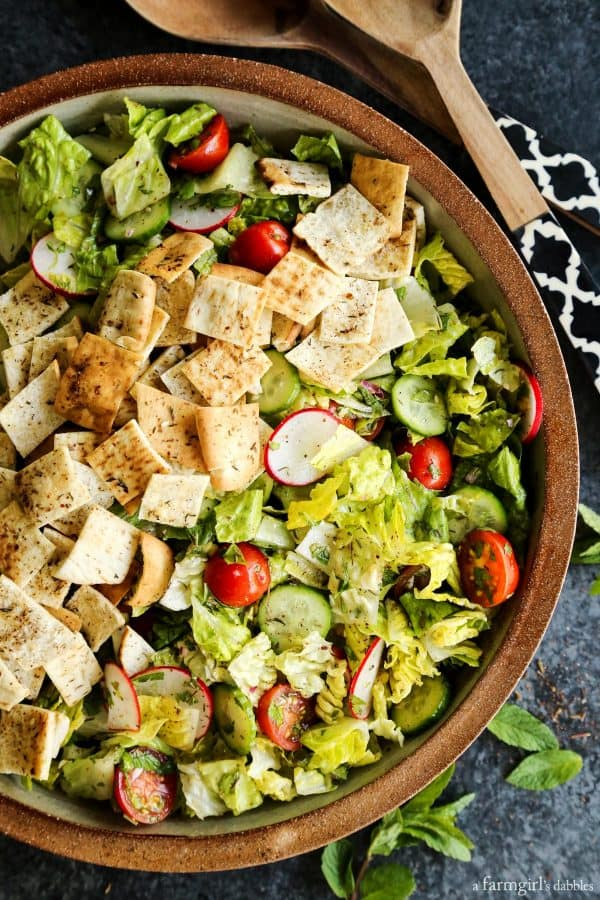 Fattoush Salad with wooden serving spoons
