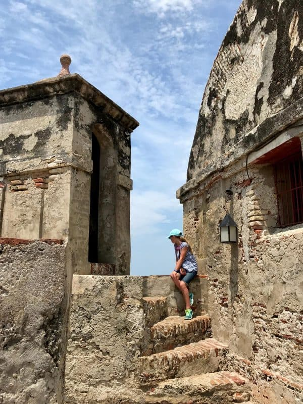 a girl sitting on steps at Castillo de San Felipe de Barajas in Cartagena, Colombia