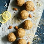 Aloha Protein Balls on parchment paper with almonds, lemon slices and coconut