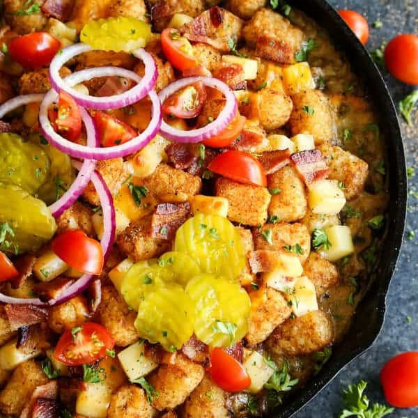 Tater tots with sliced pickles, tomatoes and red onion in a cast iron skillet