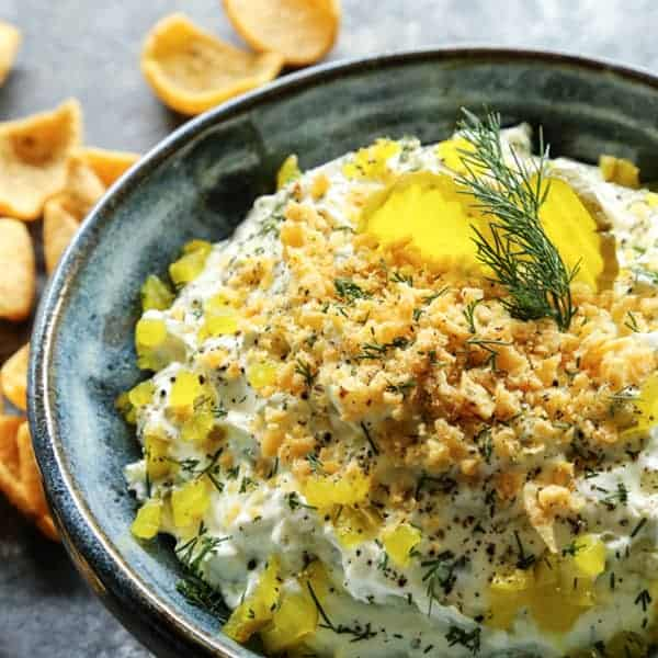 Creamy dill pickle dip topped with diced dill pickles and cracker crumbs