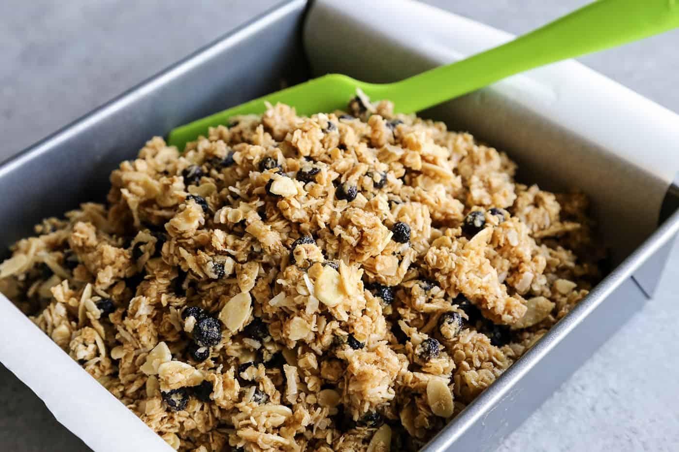 Mixing granola bar ingredients in a baking dish
