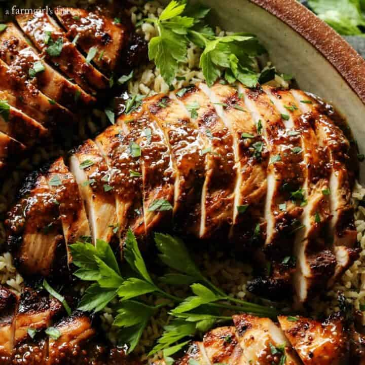 turkey tenderloin, grilled and then sliced - with brown sugar and whole grain mustard sauce, served over brown rice, on a tan pottery platter