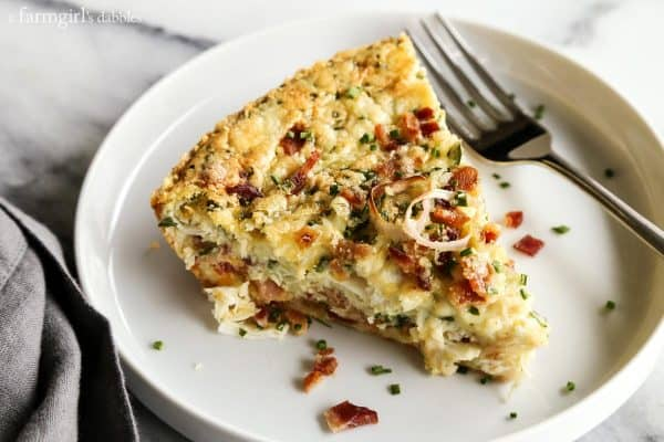 a slice of Herby Crustless Quiche with Crab and Bacon on a white plate