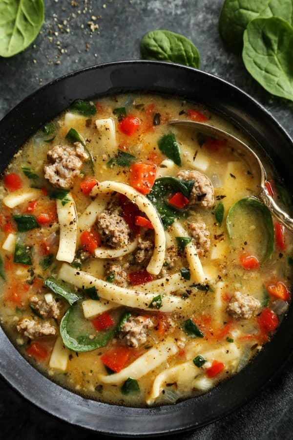 Sausage and Red Pepper Soup with Egg Noodles in a black bowl