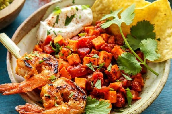 Mexican Sweet Potato and Tomato Grilled Shrimp Bowls from afarmgirlsdabbles.com - Jumbo shrimp in a spiced orange marinade, grilled to perfection, crown a bowl of Mexican-spiced sweet potatoes and tomatoes for tortilla chip dipping. Don't forget the sour cream and guacamole!