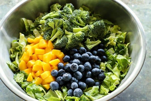 a bowl of lettuce, broccoli, blueberries, and mango