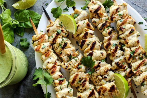 Grilled Chicken Skewers with Green Curry Yogurt Sauce from afarmgirlsdabbles.com - Flavorful marinated chicken is threaded onto skewers and grilled to perfection. Served with a green curry yogurt sauce that is bursting with fresh herbs. #chicken #grilled #grilling #skewers #kebabs #curry