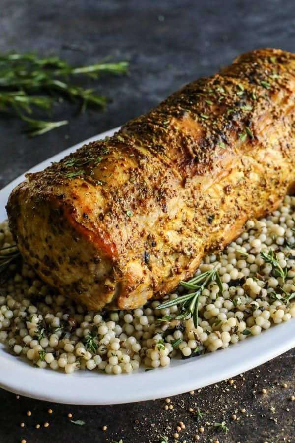 Mustard Pork Loin Roast from afarmgirlsdabbles.com - This pork loin roast is wonderfully tender and flavored with an ultra tasty mustard sauce. The dish is easy enough for a weeknight meal and definitely pretty enough to serve for holidays and special occasions. #pork #loin #roast #mustard #rosemary