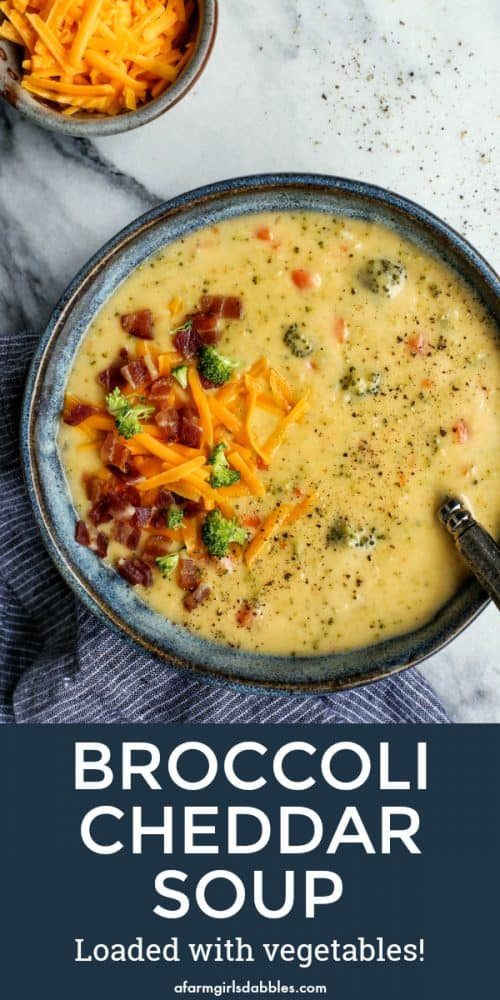 pinterest image of a blue bowl with Broccoli Cheddar Soup Loaded with Vegetables