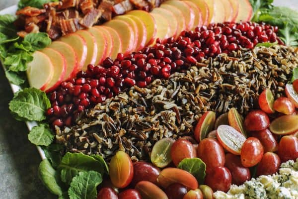 close-up photo of salad with wild rice, grapes, pomegranates, bacon, apples