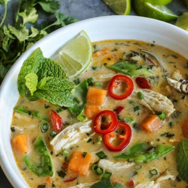 Thai Chicken Soup served in a bowl with fresh mint, lime, and peppers