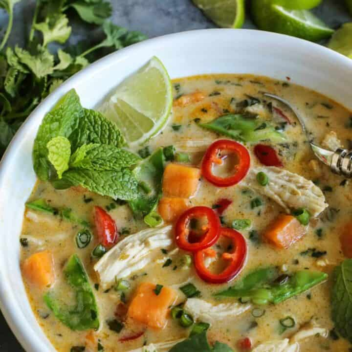 Soup with chicken and Thai flavors served in a bowl with fresh mint, lime, and peppers