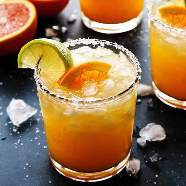 An orange margarita with fresh orange and lime wedges