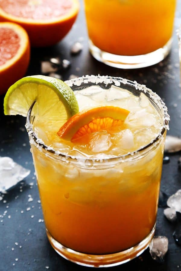 orange margarita in a glass with fresh orange and lime wedges