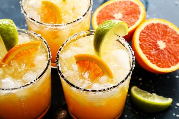 Three glasses of orange margaritas and sliced oranges