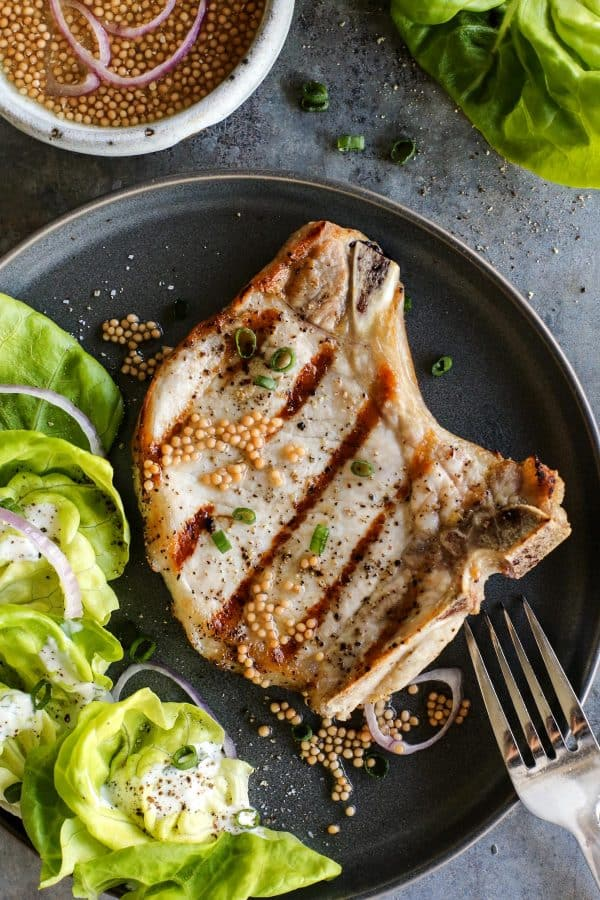 a grilled pork chop with a small side salad topped with buttermilk ranch dressing