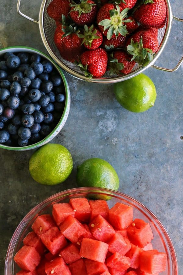 colander of strawberries, bowl of blueberries, bowl of watermelon, whole limes