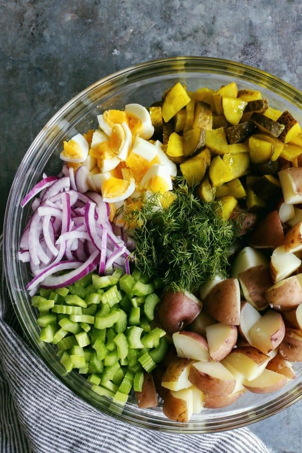 potatoes, dill pickles, hard boiled eggs, red onions, celery, dill in a clear bowl