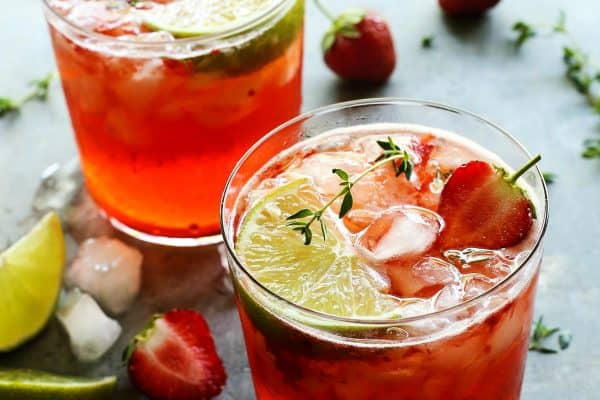 two glasses of strawberry gin and tonic with fresh strawberries and lime wedges
