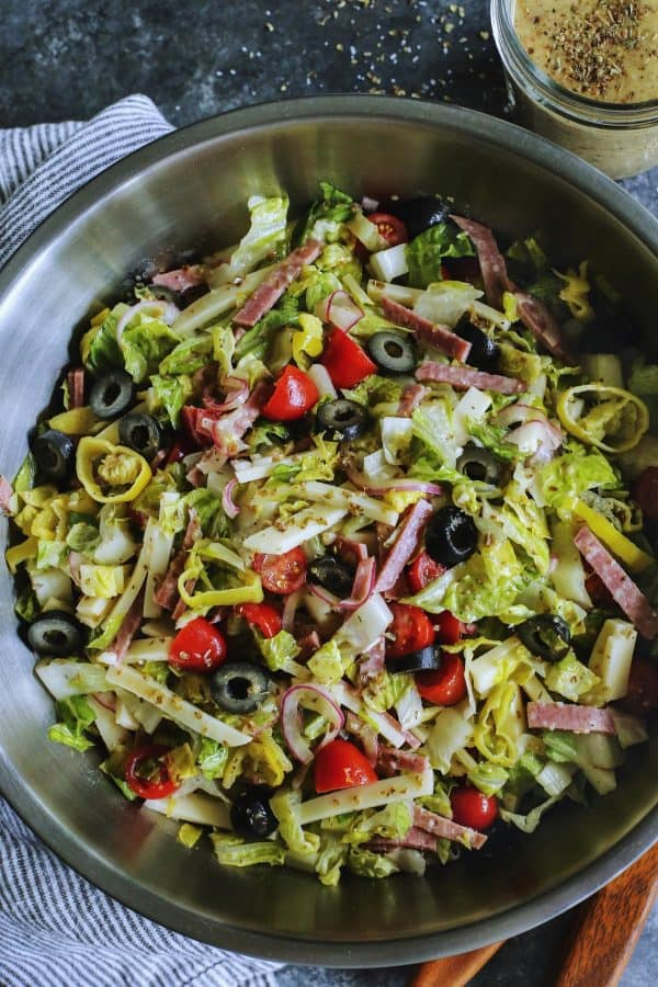 Italian chopped salad in a large stainless steel bowl, with a jar of Italian vinaigrette