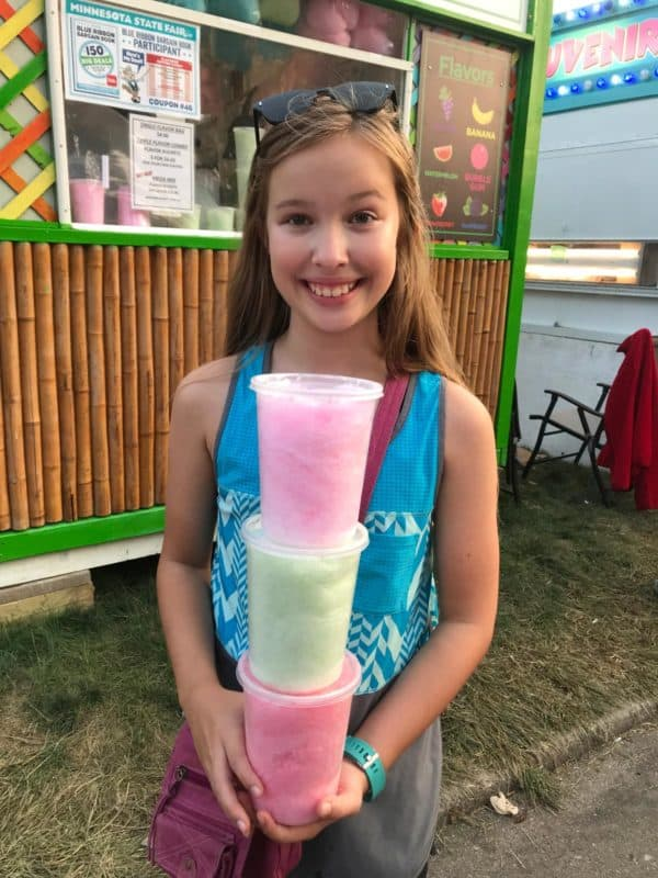 girl holding three different flavors of cotton candy in containers, from Cotton Candy 6 Different Flavors, Best Minnesota State Fair Food and Drink