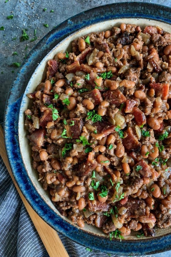 a bowl of baked beans with bacon and ground beef