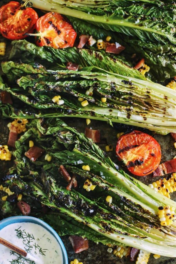 grilled romaine salad has lettuce, tomatoes, and sweet corn, with bacon crumbles and homemade ranch dressing