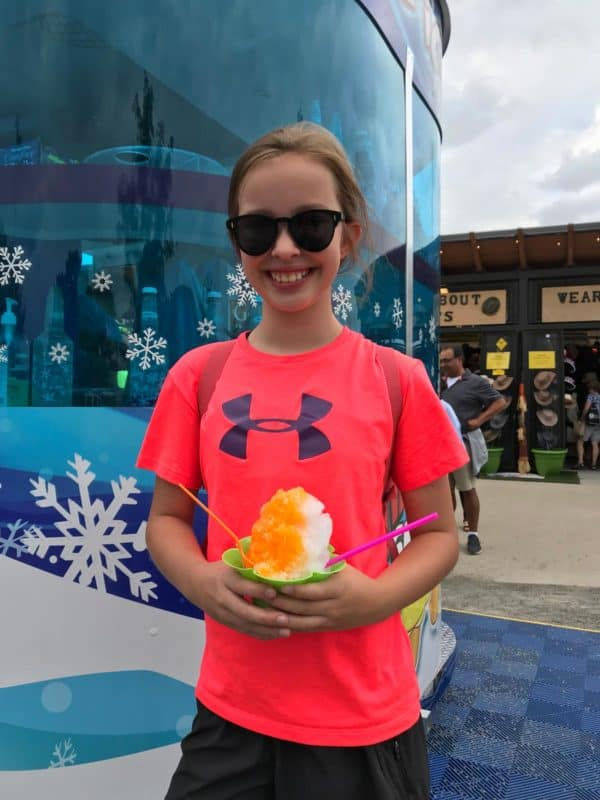 girl with sunglasses on, holding a cup of shave ice