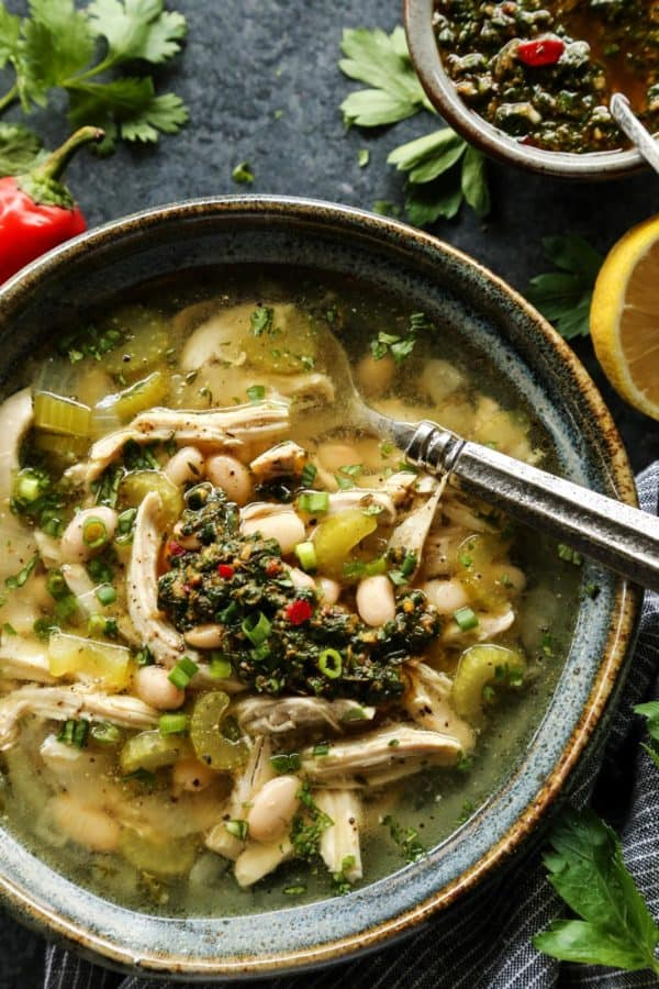 Chicken Chimichurri Soup with White Beans in a pottery bowl with spoon