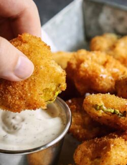 dipping a fried pickle chip into ranch dip
