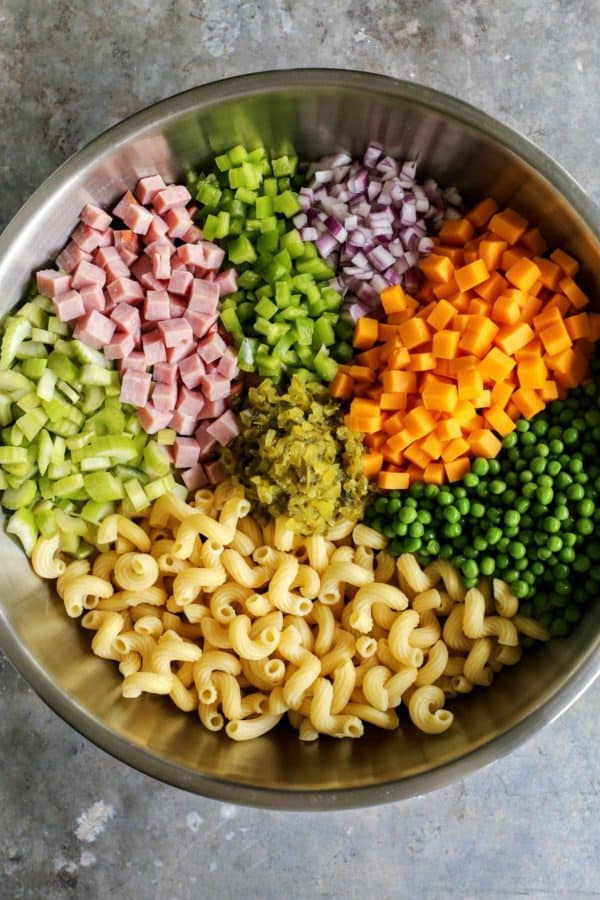 ingredients for macaroni salad - macaroni, celery, ham, green pepper, red onion, cheese, peas, pickle relish