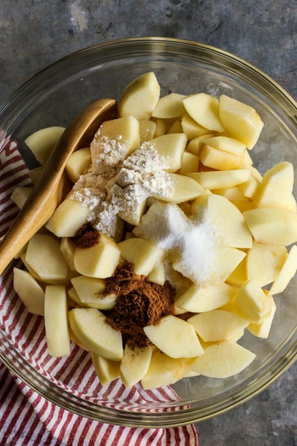 peeled apple slices in bowl with flour, sugar, cinnamon, and nutmeg