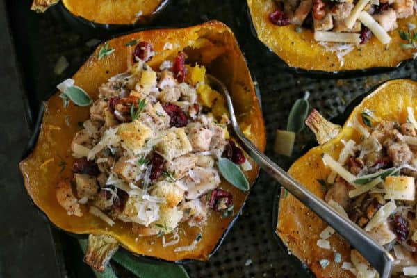 a fork in a halved acorn squash that is stuffed with a turkey and dressing mixture