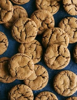 a bunch of ginger molasses cookies on a dark blue background