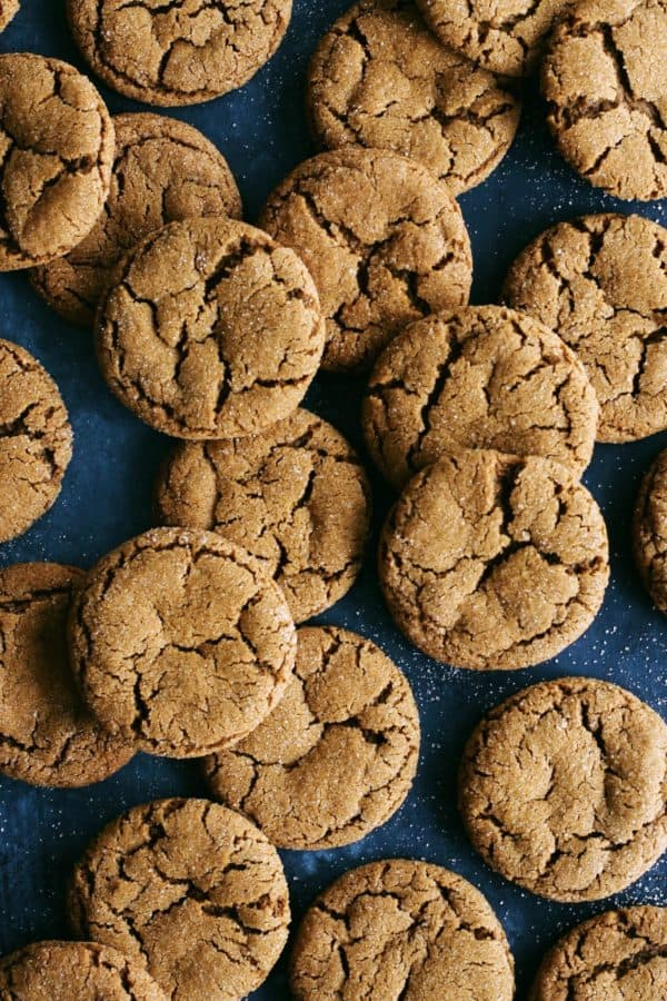 a bunch of chewy ginger cookies on a dark blue background