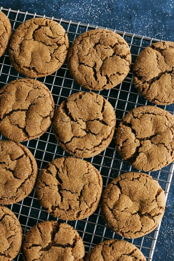 a batch of ginger molasses cookies on a cooling rack