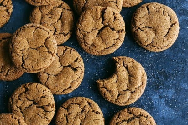 a batch of ginger cookies on a dark blue background, one cookie has a big bite out of it