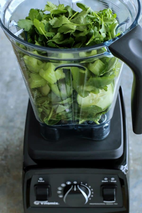 fresh green ingredients in blender pitcher