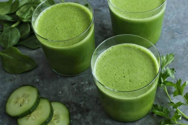 three glasses of green juice, plus fresh spinach, cucumbers, and parsley