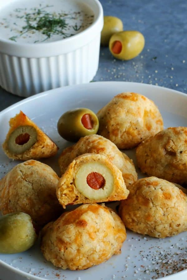 baked olive cheese balls on a plate with a cup of buttermilk ranch dip on the side
